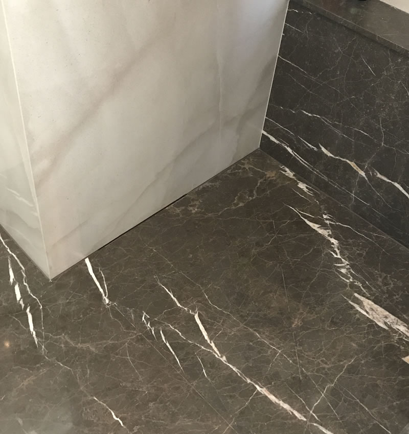 Marble tiles in a bathroom with accrued heavy water damage